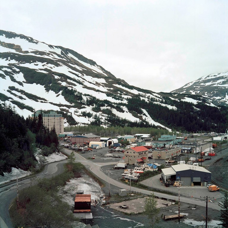 Begich Towers is seen at the left of the frame. Thirteen years after the opening of the road, Whittier still strives to grow and expand. In the works: a new road and land deal that would make private homes possible.