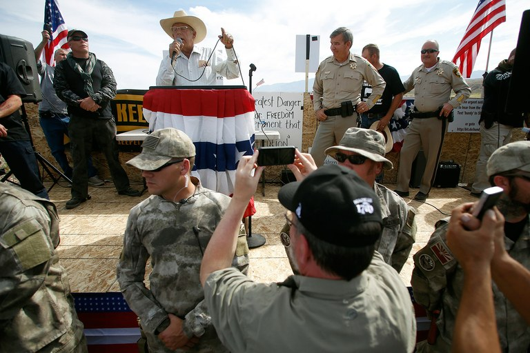 Rancher Cliven Bundy talks on stage beside Clark County Sheriff Douglas Gillespie (third from the left, on stage) in Bunkerville, April 12. Gillespie announced the BLM was ceasing its cattle roundup operation. Armed U.S. rangers had been rounding up cattle on federal land before this photograph.