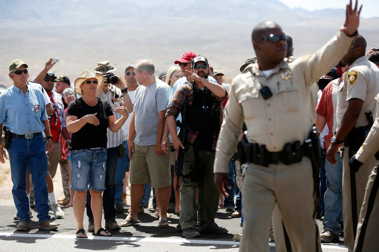 Protesters yell at law enforcement officers near the BLM's base camp where Bundy's cattle were being held, April 12. Contracted federal agents were present to preserve public safety, the safety of BLM officials rounding up cattle, and to maintain the temporary road block next to federal land.