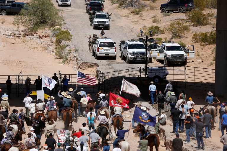 Reportedly hundreds of protesters gather at the BLM's base camp, where cattle were being held, April 12. Several U.S. military flags appear in the crowd.