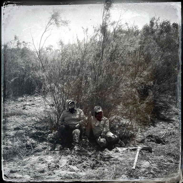 Alma-Lidia Merendon-Cerega, left, and Estela Félix-Esquivel, rest beneath the shade of an invasive tamarisk bush, which they will rip out of the ground after their break at the Laguna Grande habitat restoration site, operated by Pronatura and the Sonoran Institute in the Colorado River Delta, Baja California.