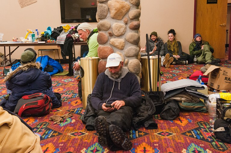 Andy Billotti, of Middletown, Maryland, checks email at the Prairie Knights casino in Cannon Ball, North Dakota on Dec. 7, 2016. Since the early days of the NoDAPL protests, the casino has been heavily used by protestors from the nearby Oceti Sakowin camp looking to connect to the outside world, shower, eat a hot meal, or sleep in a warm bed for a night. In recent days, it has also served as an emergency shelter as snow, high winds, and below freezing temperatures buffeted the region. Billotti traveled to the camp to deliver a load of donated supplies en route to Flint, Michigan, where he planned to donate a pallet of drinking water.