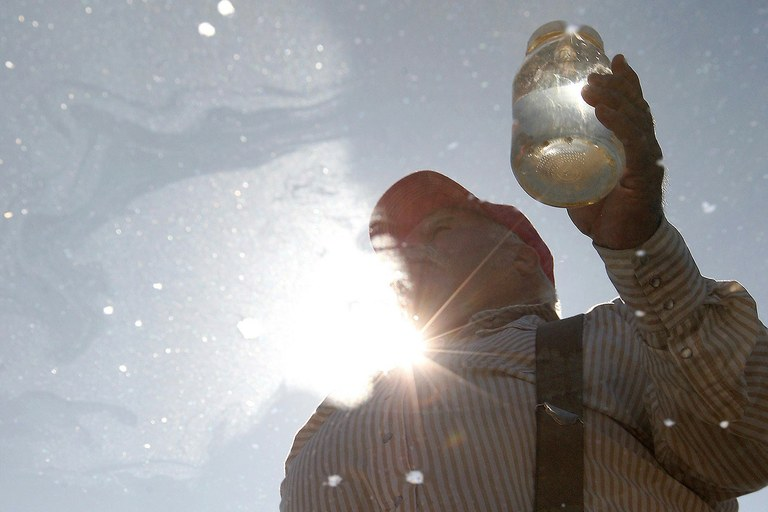 Louis Meeks holds a jar of contaminated water in Pavillion, Wyoming, where the EPA recently turned a stud