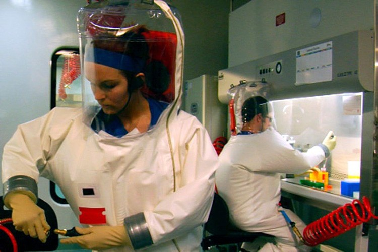 "Andrea Marzi, foreground, and Barry Rockx, practicing techniques in ""positive-pressure suits"" during a training session in a Biosafety Level 4 research suite at Rocky Mountain Laboratories"