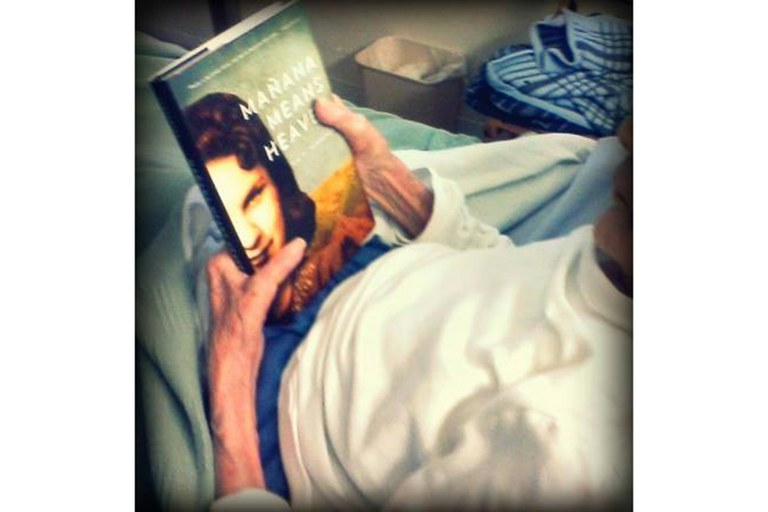 "Bea Franco staring at her own image on the cover of ""Mañana Means Heaven"" by Tim Z. Hernandez."