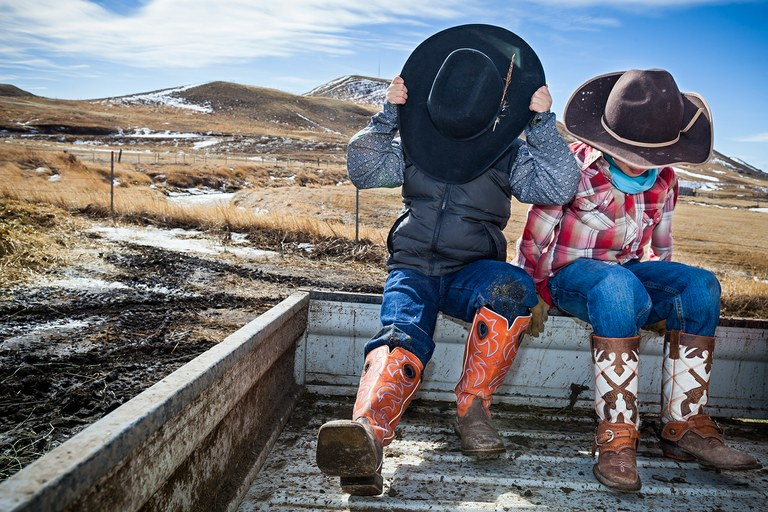 Bryson Bird, left, and Rhett Michael, both 6 years old, shield themselves from the wind on their way to assist with calving on the Rumney Ranch, 20 miles north of Browning, Montana.