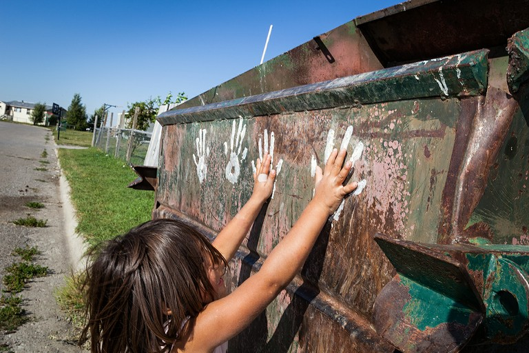 Sadie Time Sleeping, 6, compares her handprints with those left on a garbage dumpster.  Heart Butte, Blackfeet Reservation, Montana.