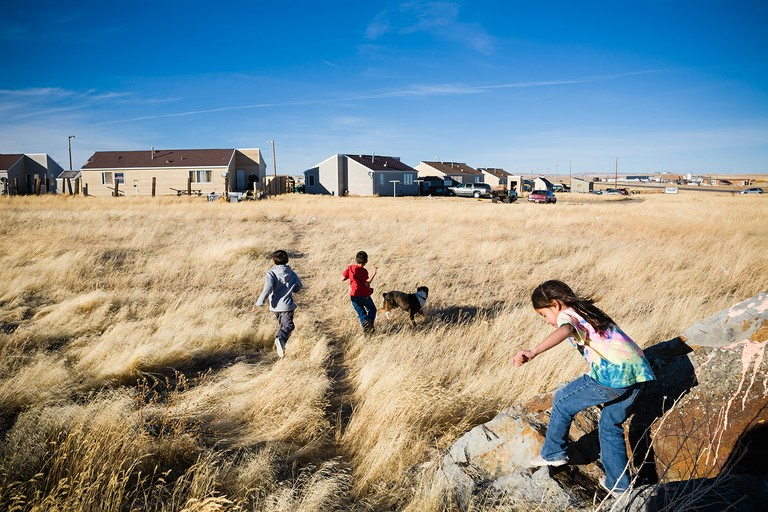 Children play outside Last Star Homes. Browning, Blackfeet Reservation, Montana.