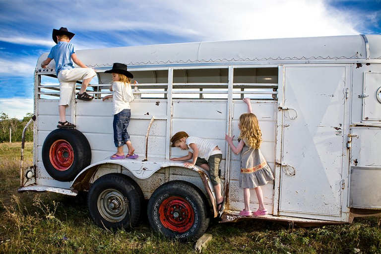 Left to right: Tyler, 6, Frankie, 5, and Jimmy and Brilee, 4, play on an old horse trailer. East Glacier, Blackfeet Reservation, Montana.