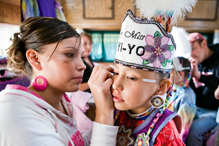 Tiffany Polk prepares her daughter, Danaya Vandeburg, for the Tiny Tot Competition at North American Indian Days on the Blackfeet Reservation in Browning, Montana.