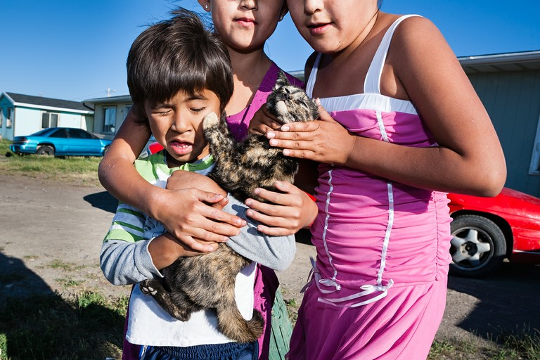 Children pose with an uncooperative kitten. Browning, Blackfeet Reservation, Montana.