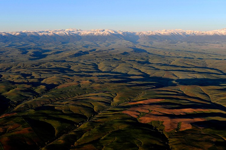 Broken hills and valleys spread out along the Beartooth Mountains in this aerial view near Absarokee, Montana. The energy company Energy Corporation of America has said it would like to make the region the next Bakken.