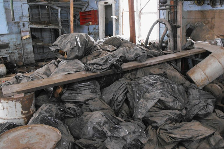 This March 3, 2014 file photo provided by the North Dakota Health Department shows bags full of radioactive oil filter socks, the nets that strain liquids during the oil production process, piled in an abandoned building in Noonan, North Dakota.