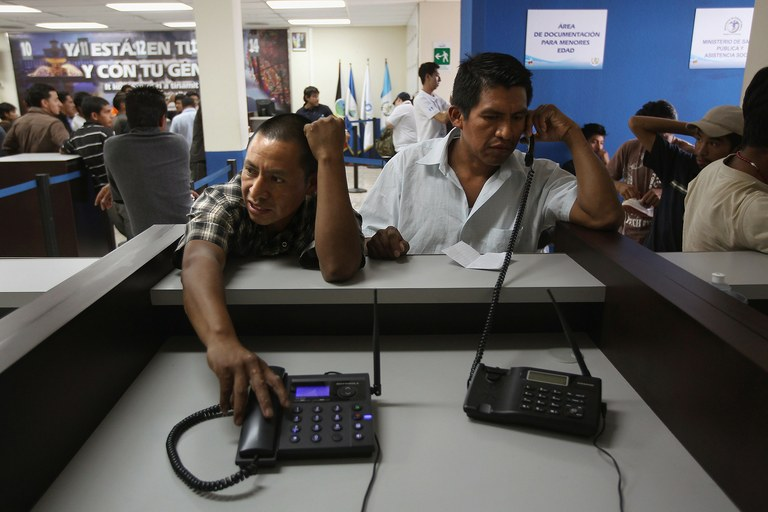 Returning Guatemalan immigrants make free phone calls to their families after arriving on a deportation flight from Arizona on June 24, 2011 to Guatemala City, Guatemala.