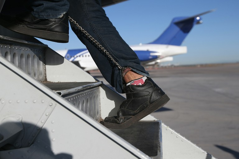 A Honduran immigration detainee, his feet shackled and shoes laceless as a security precaution, boards a deportation flight to San Pedro Sula, Honduras in Feb. 2013 in Mesa, Arizona. ICE operates 4 to 5 flights per week from Mesa to Central America, deporting hundreds of undocumented immigrants detained in western U.S. states.