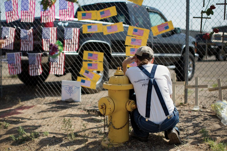 Stephen Grady reads memorial notes left at the Granite Mountain Interagency Hotshot Crew fire station in Prescott, Arizona. Nineteen members of the crew were killed in late June when a windblown wildfire overcame them north of Phoenix.