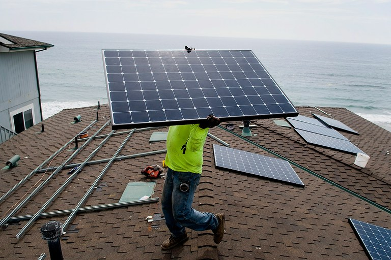 Andres Quiroz, an installer for Stellar Solar, carries a solar panel during installation at a home in Encinitas, Calif. in 2012. Stellar Solar installs residential and commercial solar panels in the San Diego area.