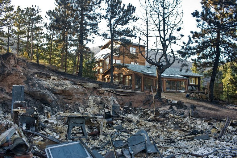 The wreckage of a burned structure sits near a surviving home after the 2010 Fourmile Canyon Fire near Boulder, Colorado. The 7,000 acre fire claimed nearly 170 houses in the first days of the blaze. Several of the houses that were saved had properly prepared their land for the potential of wildfire, including building with fire resistant materials as well as preparing defensible, fuel-minimized spaces in the areas surrounding the structure.