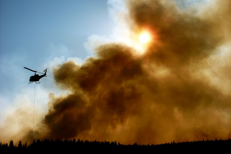 A helicopter battles a forest fire in Yellowstone National Park. Scientists believe climate change could increase the frequency of Yellowstone's fires over the next century, potentially turning many of its forests to grasslands.
