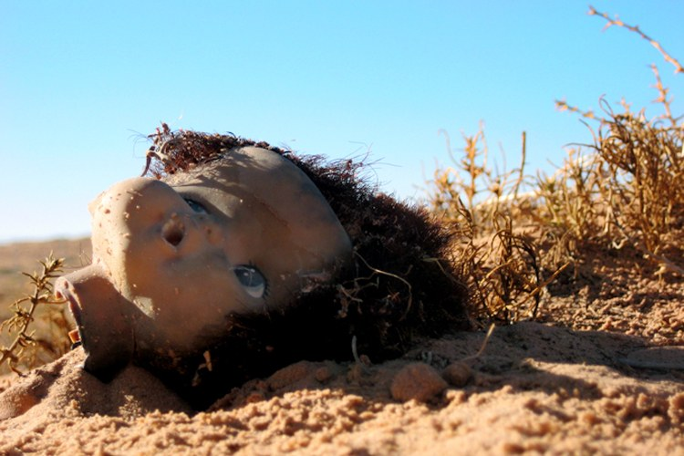 An old baby's doll emerges from the Tuba City Open Dump, an unlined and unregulated municipal disposal site on Hopi and Navajo lands. Groundwater beneath the site contains high levels of uranium that threatens the local drinking water supply. Tribal members, regulators, and operators struggle to locate the source of the contamination and ponder connections with the nearby uranium mill and the thousands of abandoned uranium mines scattered across the Navajo Nation.