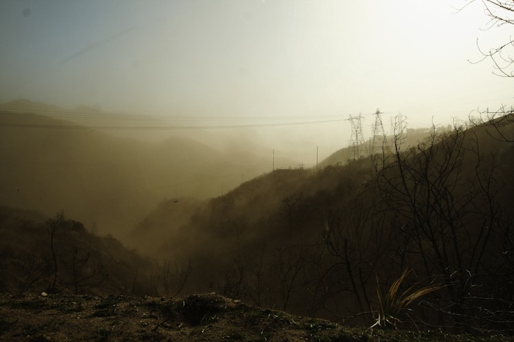 A severe dust storm in the San Gabriel Mountains, the frontier of development outside the metropolitan area of Los Angeles, California. The dust storm occurred after fires swept through the area.