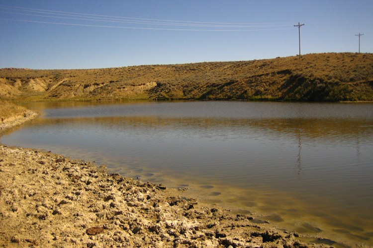 Impoundments like this one dot the Powder River Basin of northeastern Wyoming. These small ponds hold water produced by coalbed methane extraction. This water, which must be pumped from deep aquifers in order to access gas, is often saline or otherwise unsuitable for agriculture and wildlife. Disposing of the water without contaminating shallow aquifers or disturbing stream flows and water quality is one of the biggest challenges involved in coalbed methane extraction. Building impoundments is a common strategy, though not without its problems.