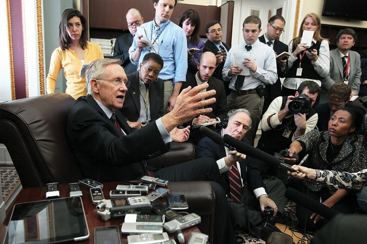 In April, U.S. Senate Majority Leader Sen. Harry Reid holds court with members of the press during a news briefing on Capitol Hill.