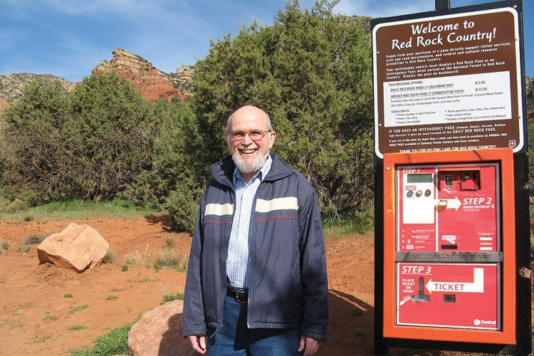 Retired geophysicist Jim Smith stands next to a Red Rock Pass dispenser at a trailhead just outside Sedona, Arizona.