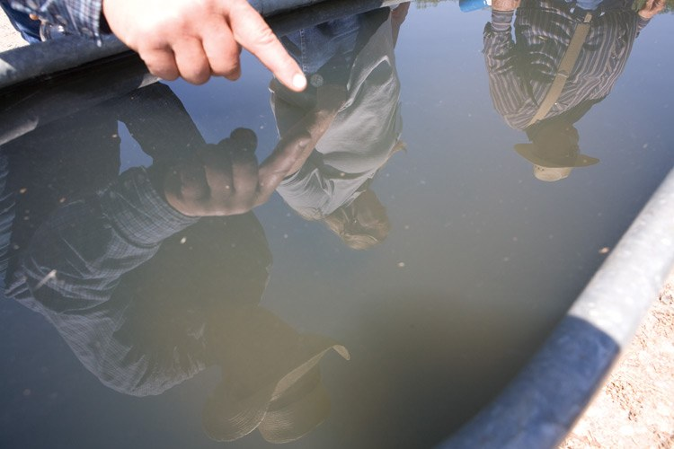 John Fenton and Donna and Louis Meeks are reflected in a tank containing contaminated water from the Meeks well.  The EPA has sampled the well water and found chemicals associated with natural-gas drilling, including benzene, toluene and methane, and warned the Meekses and others to not drink the water.