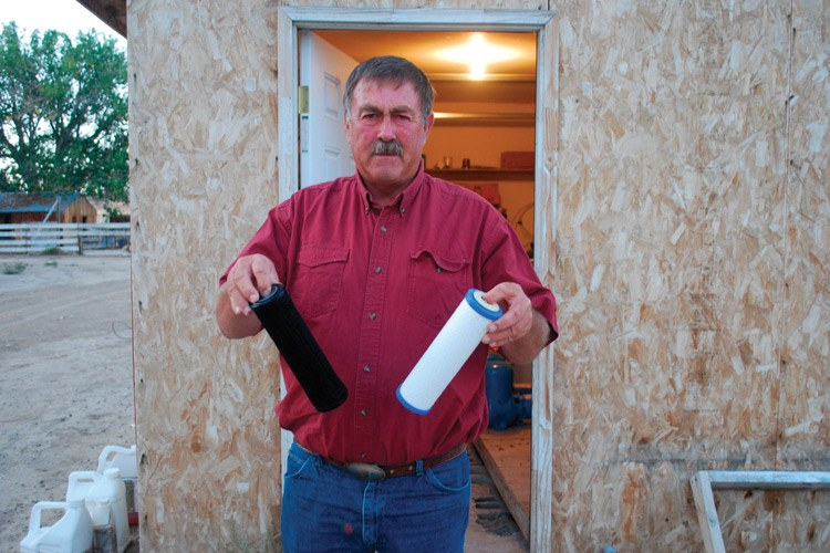 Jeff Locker, a neighbor of the Meekses, displays water filters from the well filtration system a drilling comp
