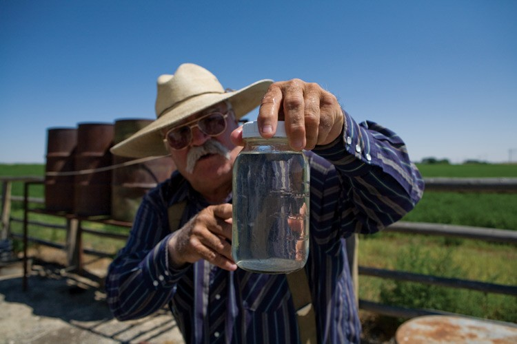 Louis Meeks of Pavillion, Wyoming, holds a jar of tainted water from his well. He believes the contamination is a result of nearby natural gas drilling, particularly hydraulic fracturing.