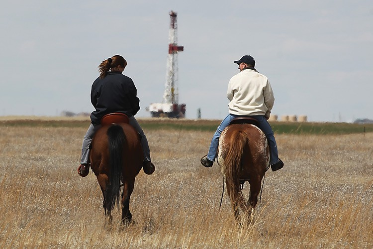 Holli and Patrick Guillory ride  near their home south of Hillsdale, Wyoming, where the increase in drilling operations -- sparked by global demand and international investment -- has them worried.