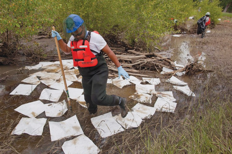 Workers use absorbant pads to collect oil in the Yellowstone River floodplain after an Exxon Mobil pipeline failed, spilling oil into the river.