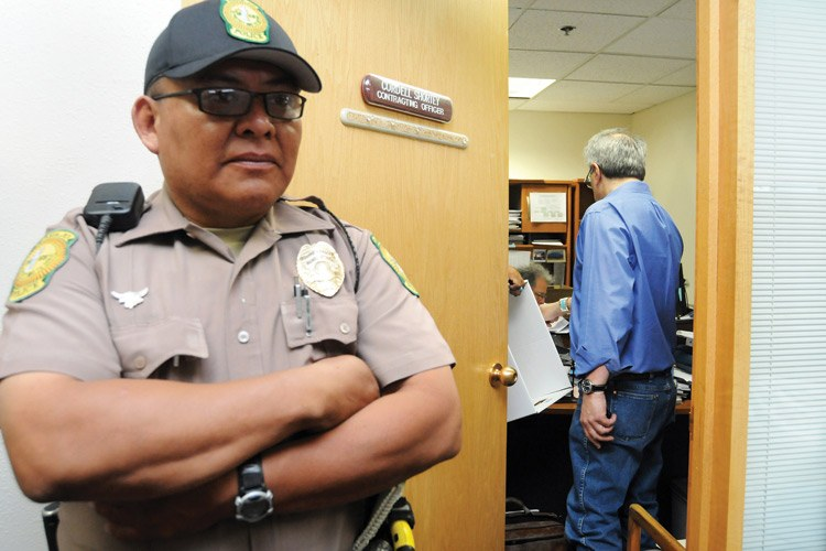 An officer stands guard as Special Prosecuter Alan Balaran (blue shirt) and investigators from the tribal attorney general's office conduct a search-and-seizure warrant in May at the Office of the Management and Budget and Controller in Window Rock.