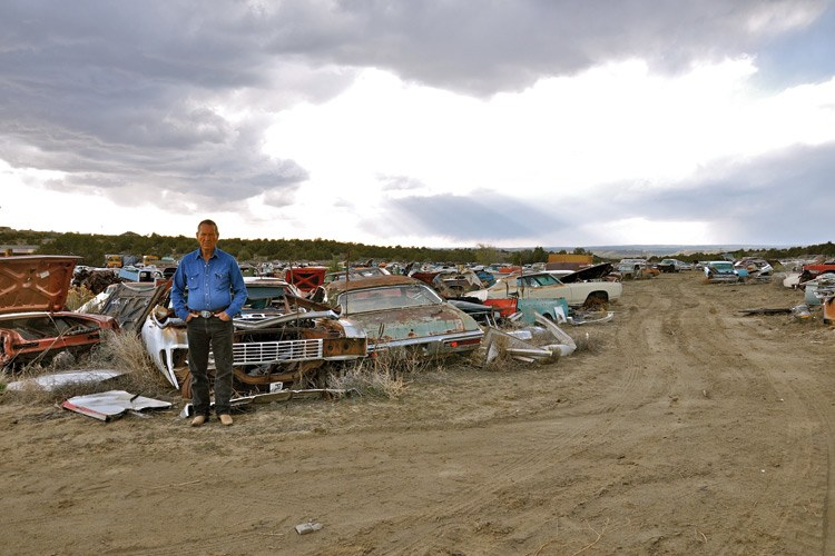 Carl Bannowsky with some of the 500 junk cars he keeps behind his doublewide in northern New Mexico.