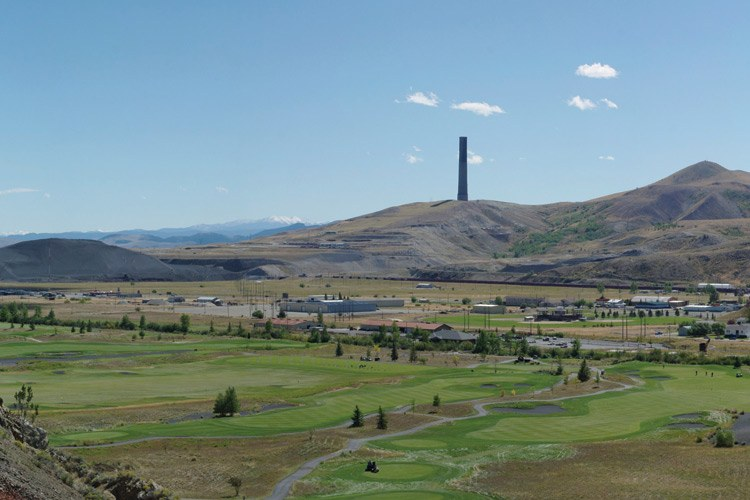 Anaconda, Montana, looking south from the Old Works smelter site across the Old Works golf course, with its repurposed black smelter slag in the sand traps, toward the Anaconda smelter stack on the horizon.