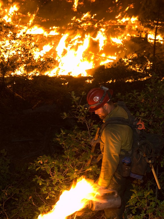 A member of the Kings River Hotshots' Division T performs a night burn operation during the Las Conchas Fire