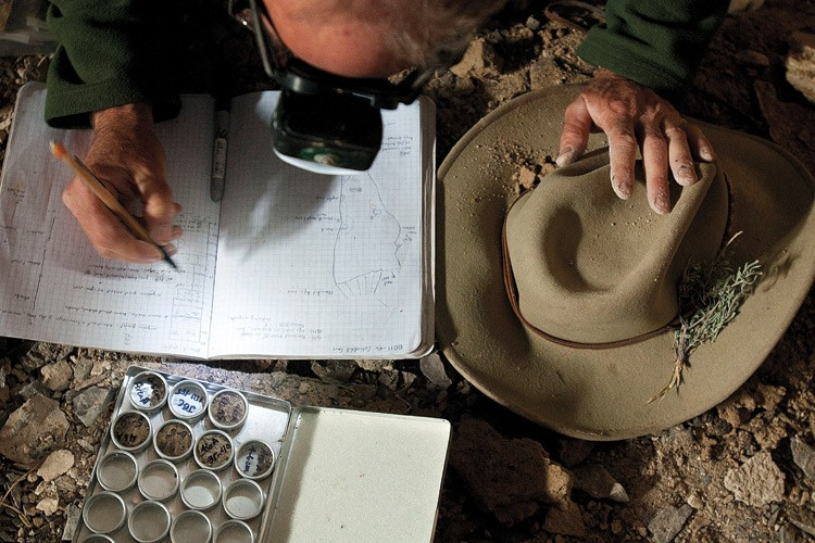 Jay Quade jots down notes about silt layers buried in the floor of Cathedral Cave. The vials hold snail shells, fish bones, and other samples for radiocarbon dating.