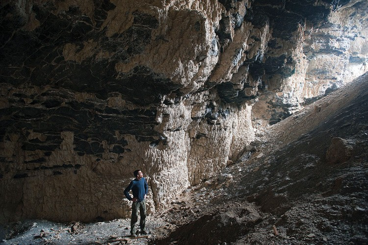 The University of Minnesota's David McGee gazes toward the entrance of Cathedral Cave, which once sat as far as 750 feet below the surface of Lake Bonneville. Lightcolored tufa stone coats the inside of the cave. It was laid down thousands of years ago by algae that grew in sunlight filtering in through the then-submerged