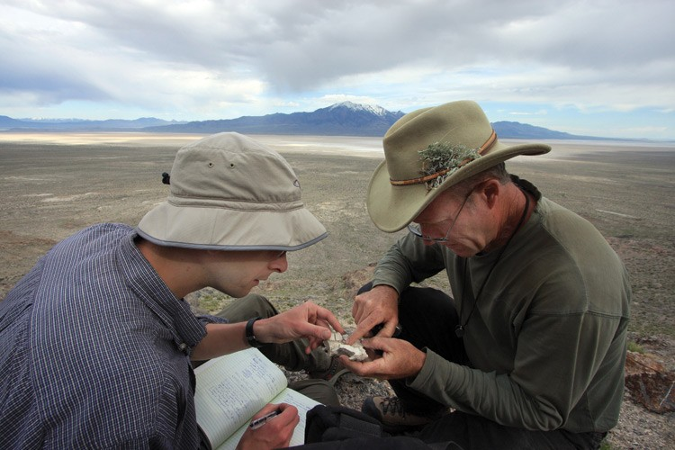 David McGee, left, and Jay Quade, sitting near a shoreline around 600 feet above the valley floor, examine a mineral crust fragment left behind by Lake Bonneville on the slopes of the Silver Island Range.