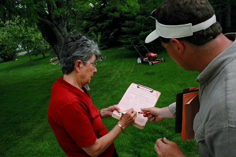 A voter signs a petition for a Montana ballot initiati