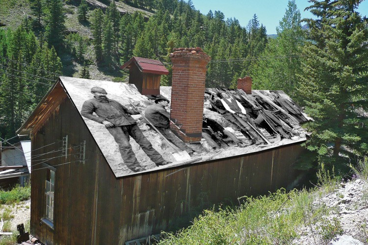 A photo illustration shows an idea for a temporary fix to help the mine's fragile structures survive the next winter: a roof-covering tarp depicting miners.
