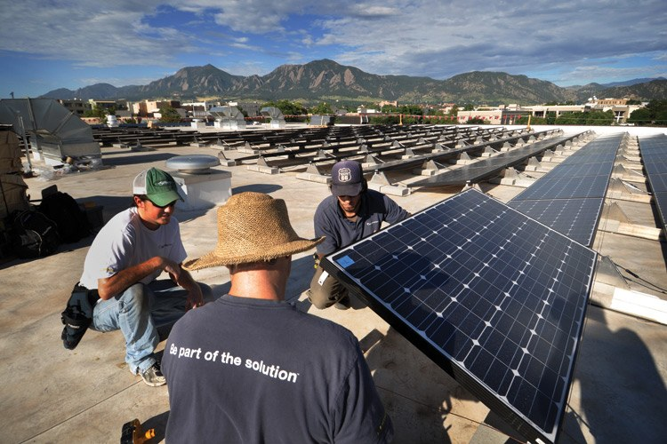 Workers install solar panels last year on the roof of the University of Colorado Center for Innovation and Creativity in Boulder.