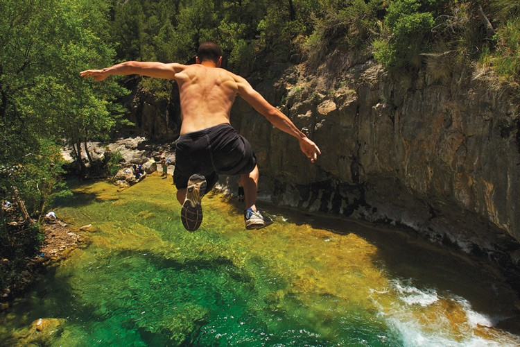 A man jumps from a cliff into a pool in Fossil Creek as others look on.