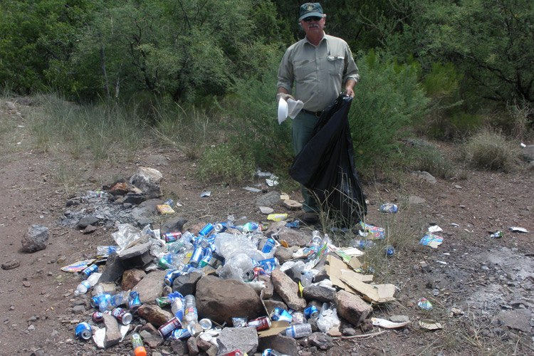 Dexter Allen, a Fossil Creek patrol ranger, cleans trash from a firepit after a big weekend.