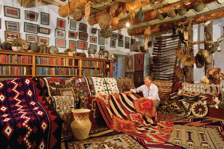 Billy Malone, Indian trader, in the Rug Room of Hubbell Trading Post in the early 1990s, with historic and modern Navajo Indian  weavings.