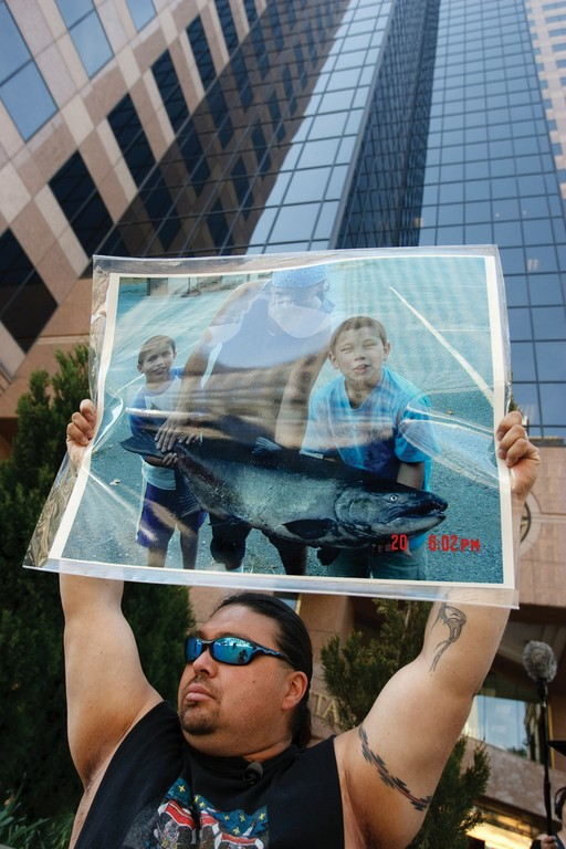 Merv George of the Karuk Tribe, at a protest in front of PacifiCorp's Salt Lake City offices, holds a photograph of a traditional Karuk fisherman and his sons holding a salmon.