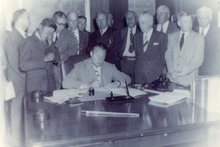 Tribal Chairman George Gillette, front left, weeps as Interior Secretary Julius Krug signs reservation land over to the U.S. government for the Garrison Dam.