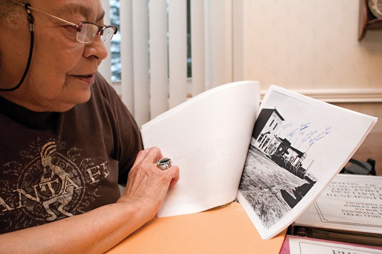 Marilyn Hudson looks at an annotated photocopy of a photo of the town of Sanish before the flood.  Hudson has been working with residents of the former town to identify buildings and other landmarks lost when the dam was built.