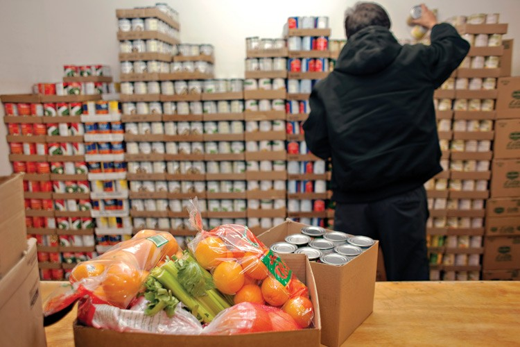 A worker fills an order for a family at the commodity distribution center in New Town, where fresh fruit and vegetables are delivered every Monday.